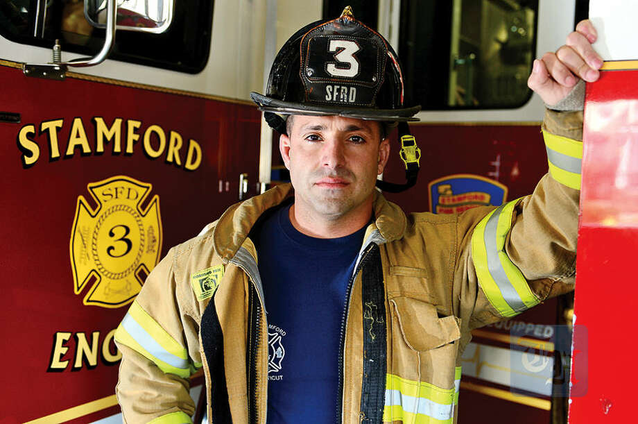 Hour photo / Erik Trautmann Stamford firefighter Rocco Terenzio, 34, saved a Greenwich man while off duty in March. Terenzio heard a loud explosion from the victim's house and ran in there and saved him within five minutes.
