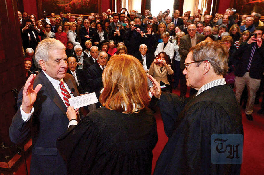 Hour photo / Erik Trautmann Norwalk Judge of Probate Antony DePanfilis gets sworn in for his last 4 year term by Superior Court Judges Eddie Rodriguez and Maureen Dennis during a ceremony at Lockwood Mathews Mansion Wednesday morning.