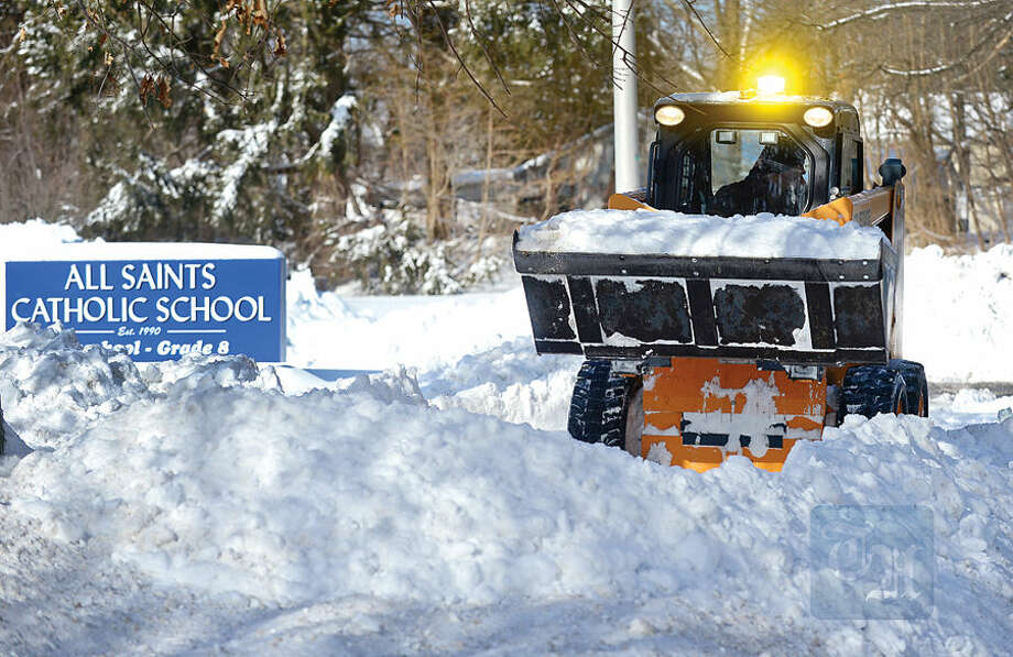Hour photo / Erik Trautmann maintenance crews remove snow from the sidewalks outside All saints Catholic School on West Rocks Rd Tuesday.
