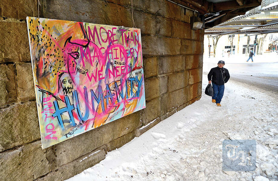 "Hour photo / Erik Trautmann A pedestrian walks by newly installed graffiti on canvas under the Washington St train bridge that reads, ""More Than Machines, We Need Humanity"" in SoNo Tuesday."