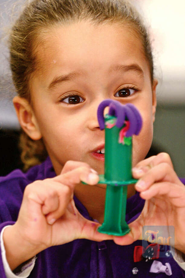 Hour photo / Erik Trautmann Liliana Gomez, 5, squeezes out Play-Doh during the Play-Doh Palooza at the a SoNo Branch Library Friday. The activity was a SoNo Branch Library Kids Build Program to help foster creativity.