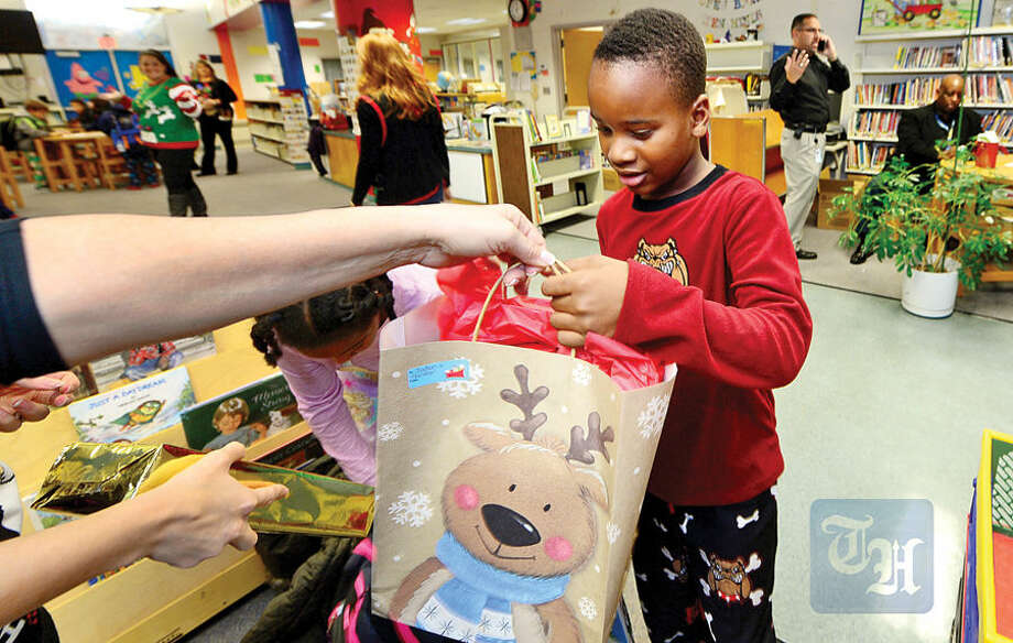 Hour photo / Erik Trautmann Students at Fox Run Elementary School students, including 2nd grader Jaden Stephenson, receive presents through the generosity of Walmart General Manager KelvinBernadine, who donated enough toys for nearly 100 needy students Wednesday.