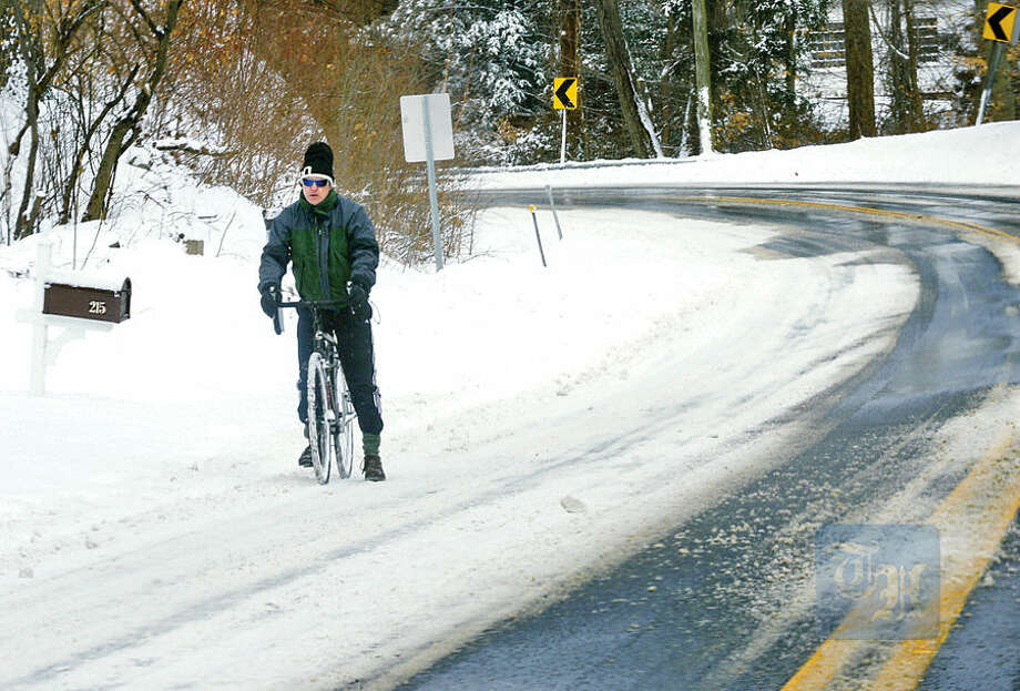 Hour photo / Erik Trautmann A bicyclist tries to navigate Wilton Rd in Westport after the blizzard that hit the area Tuesday.
