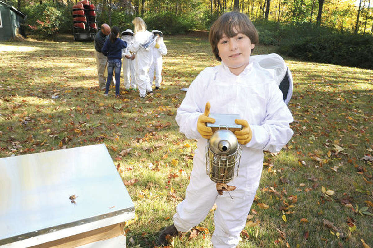 Eli Busch, a sixth-grader at Montessori School in Wilton, with his smoker helps take care of the bee colony on the grounds of the school.