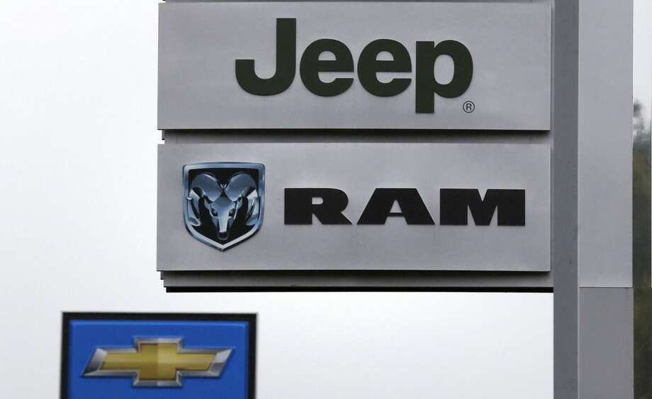 This Oct. 1, 2014 photo shows Jeep, Dodge Ram and Chevrolet logos on signs at Bill DeLuca's dealerships in Haverhill, Mass. Chrysler, Nissan and Honda on Monday, Nov. 3, 2014, all reported U.S. sales gains last month as low gas prices and booming SUV and pickup truck sales drove people into dealerships. (AP Photo/Charles Krupa)