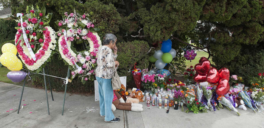 A woman visits the street-side memorial at North Jacaranda Street and Fairhaven Avenue in Santa Ana, Calif. on Saturday, Nov. 1, 2014 for three teenage trick-or-treaters killed in a Friday night hit-and-run accident. (AP Photo/Orange County Register, Ken Steinhardt)