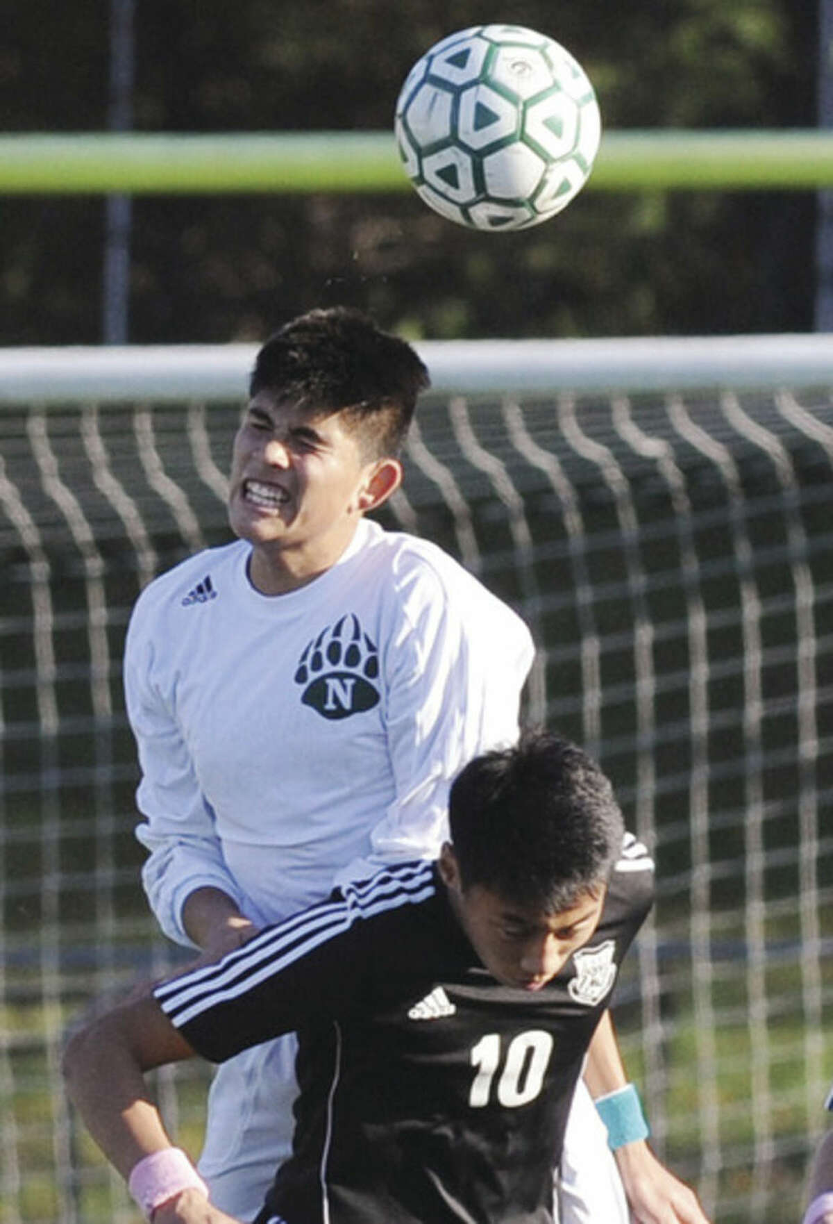 Hour photo/Matthew Vinci Norwalk's Alex Escalante jumps to head a b all over Trumbull's Thang Dao during Monday afternoon's Class LL state tournament game in Norwalk.