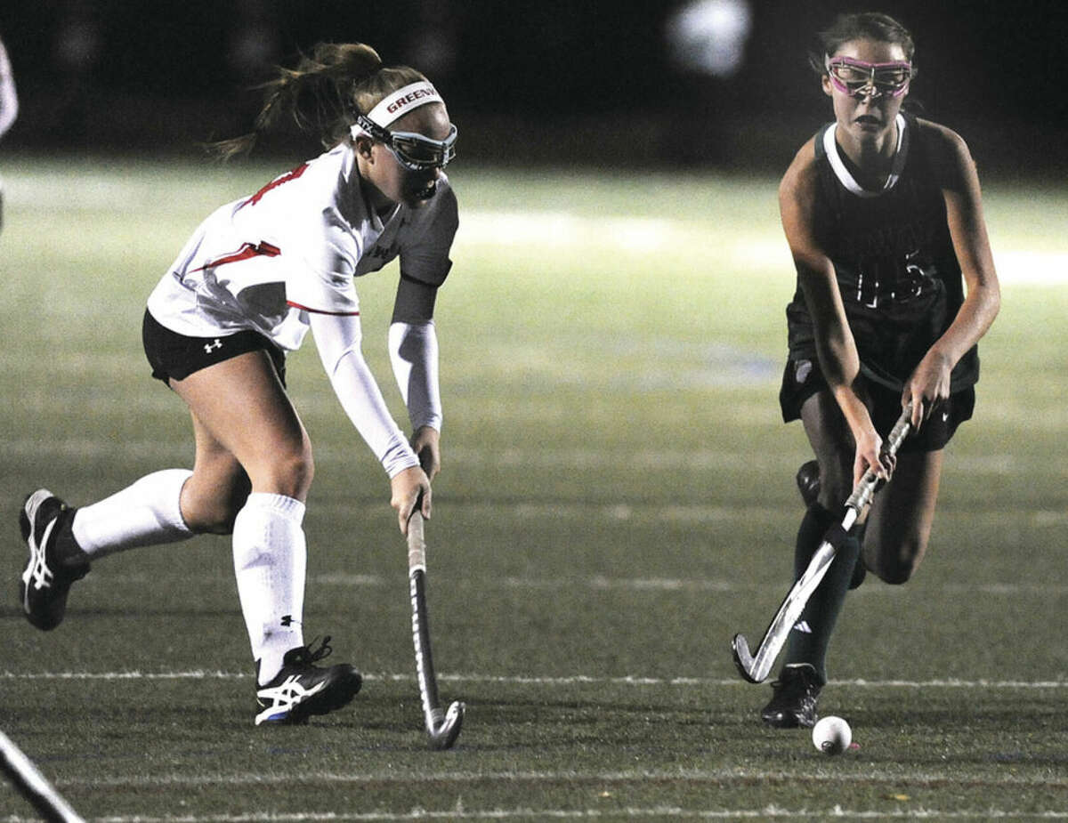 Hour photo/Matthew Vinci Norwalk's Kristen Carriera brings the ball up field during Monday's Class L state tournament game with Greenwich's Anne Dunster in pursuit.