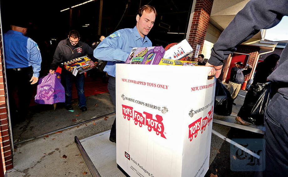 Hour photo / Erik Trautmann Wilton firefighters including Glenn Johnson, police officers and students from Lady of Fatima School help Toys for Tots volunteers load toys from the donation drop boxes located throughout Wilton at Fire Headquarters Wednesday morning.