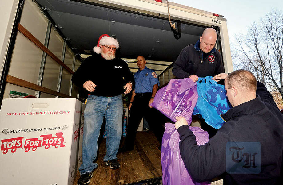 Hour photo / Erik Trautmann Wilton firefighters including Don Scarpetti and Dan Lewis, police officers and students from Lady of Fatima School help Toys for Tots volunteer Peter Havens load toys from the donation drop boxes located throughout Wilton at Fire Headquarters Wednesday morning.