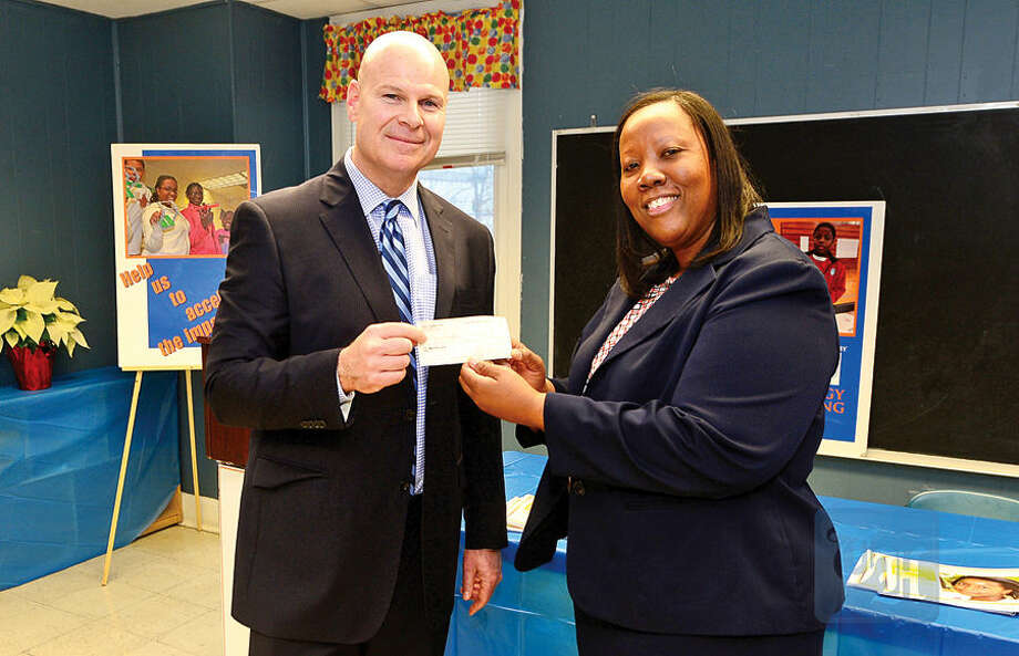 Hour photo / Erik Trautmann Carver Community Center Executive Director Novelette Peterkin receives a check from Mark Feinberg, nephew of the private donor, for $472,000, which was bequeathed to build the new Charlotte Naomi Horblit Technology Center following a press conference Thursday.