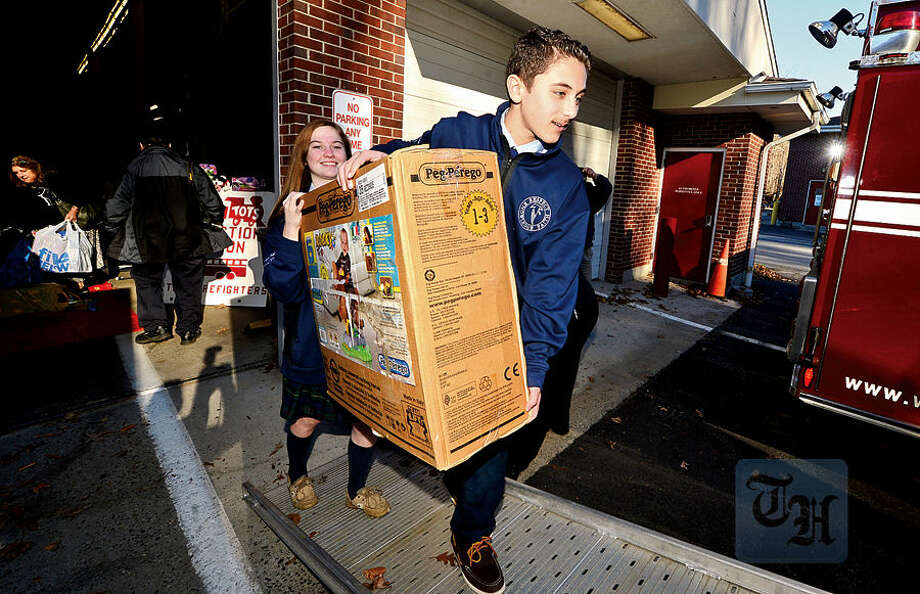 Hour photo / Erik Trautmann Wilton firefighters, police officers and students from Lady of Fatima School including 8th graders Lauren Oskam and David Zahrah help Toys for Tots volunteers load toys from the donation drop boxes located throughout Wilton at Fire Headquarters Wednesday morning.