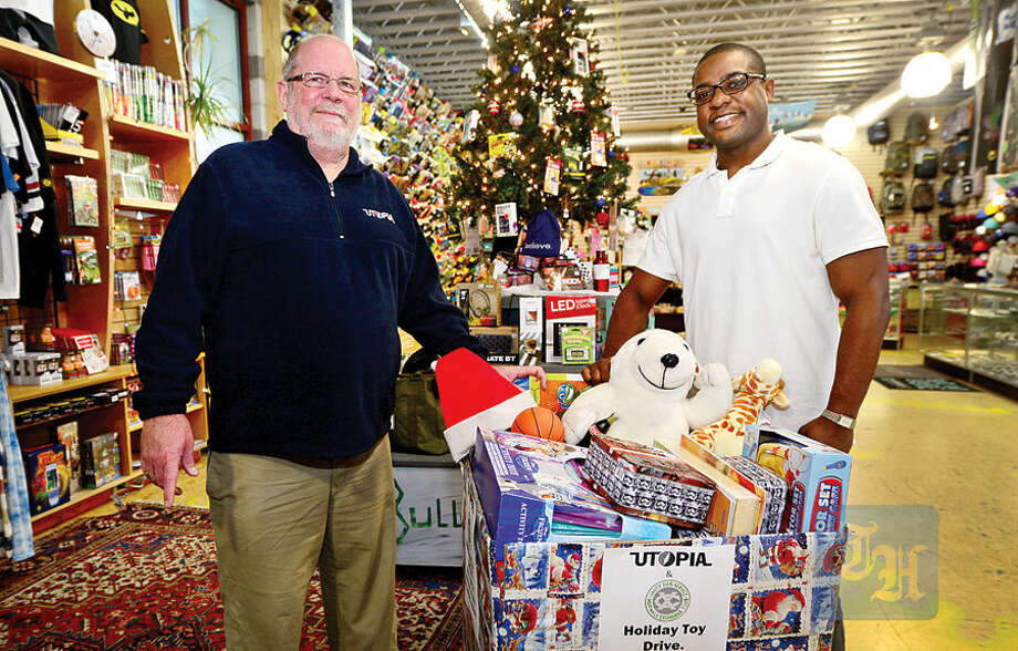 Hour photo / Erik Trautmann Utopia owner Ray Cooke and Ernst Turnier of the Norwalk Exchange Club partner up for a Christmas Toy Drive this year.