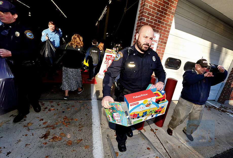 Hour photo / Erik Trautmann Wilton firefighters, police officers including officer Steve Sisenstein and students from Lady of Fatima School help Toys for Tots volunteers load toys from the donation drop boxes located throughout Wilton at Fire Headquarters Wednesday morning.