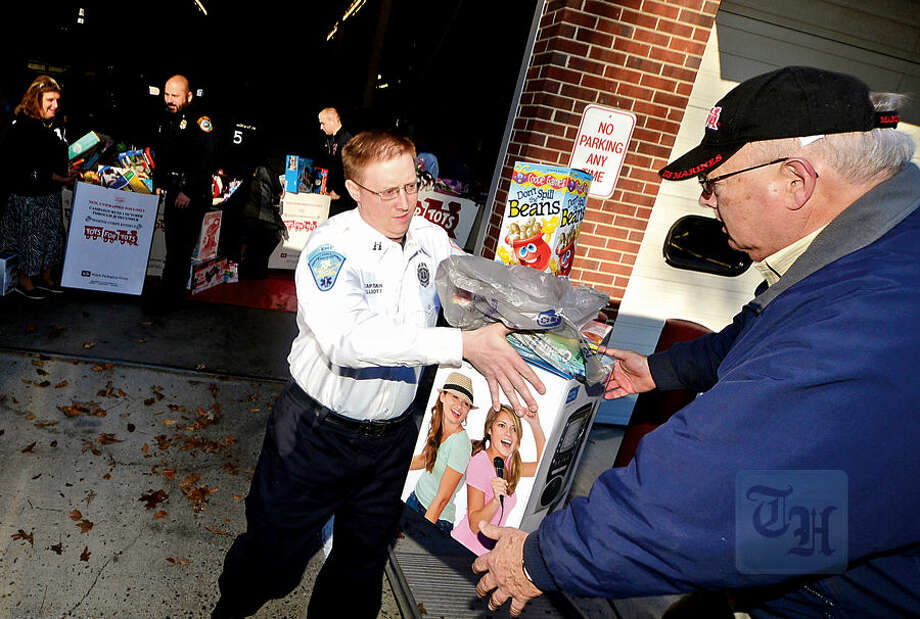 Hour photo / Erik Trautmann Wilton firefighters including Captain Brian Elliott, police officers and students from Lady of Fatima School help Toys for Tots volunteers load toys from the donation drop boxes located throughout Wilton at Fire Headquarters Wednesday morning.