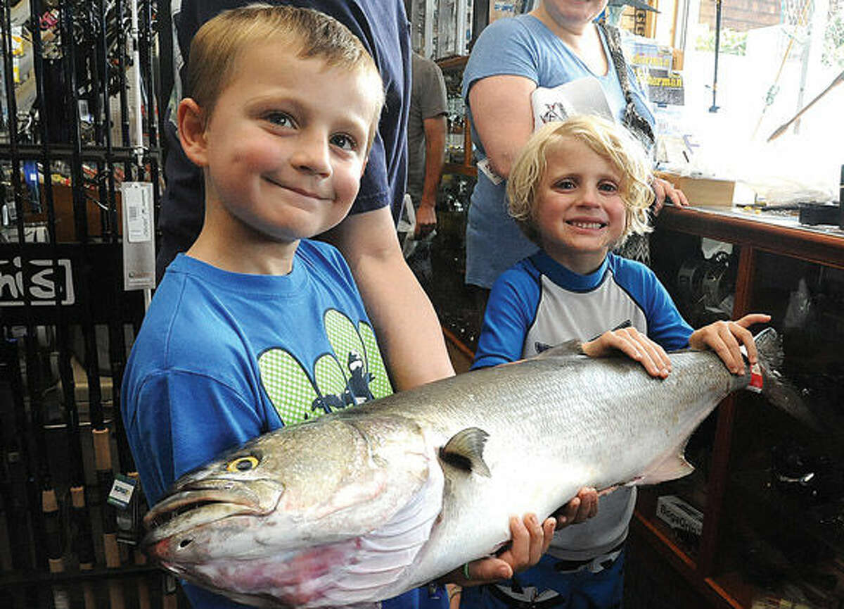 Casey Bumbulis 8, and his little brother Finn 6, with a 13 lbs bluefish Sunday at Fisherma's World in Norwalk. The fish was caught by local fisherman Jason Vlicky and at noon on Sunday it was current port prize catch in the store from the Bluefish contest. Hour photo/Matthew Vinci