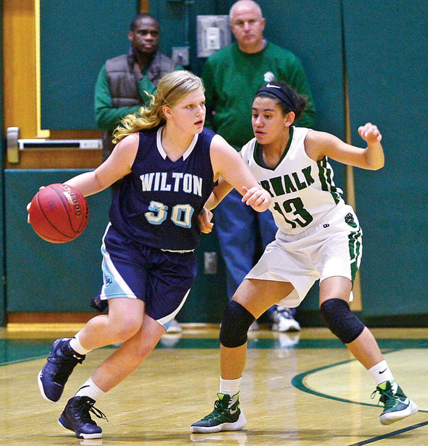 Hour photo / Erik Trautmann Wilton High School's #30 Claire Gulbin goes past Norwalk's #13 Ashley Wilson during their match up Wednesday.