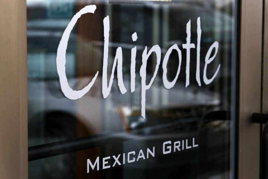 FILE - This Jan. 28, 2014, file photo, shows the door at a Chipotle Mexican Grill in Robinson Township, Pa. Chipotle's shares fell $18.58, or 3.5 percent, to $503.66 after the fast food chain disclosed additional cases of E. coli had occurred from their restaurants. (AP Photo/Gene J. Puskar, File)