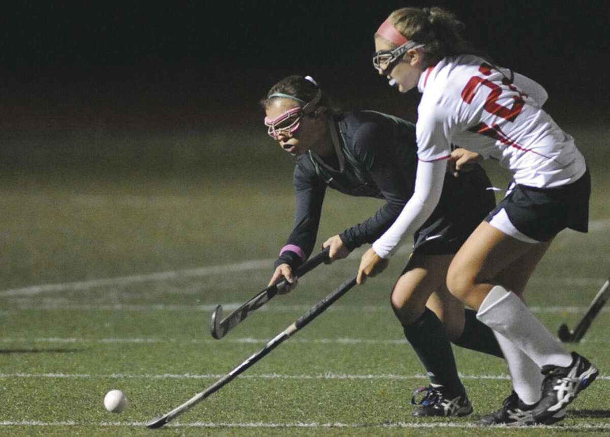Hour photo/Matthew Vinci Norwalk's Grace Bradley makes a pass while Greenwich's Sophia Poerera defends during Monday night's state tournament game.
