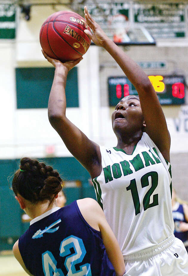 Hour photo / Erik Trautmann Norwalk High School's #12 Asiah Knight goes past Wilton's defense to the hoop during their match up Wednesday.
