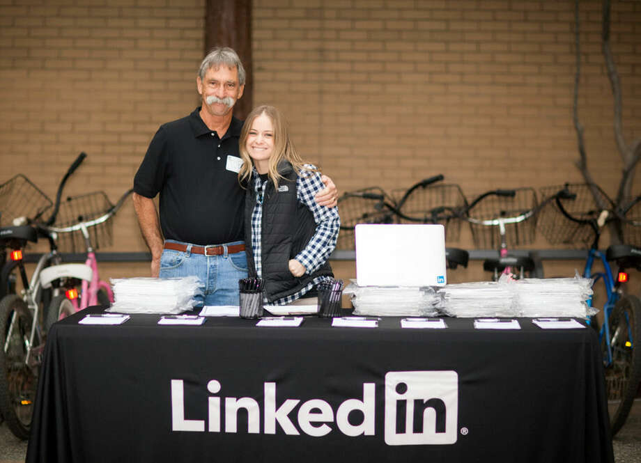 In this Nov. 7, 2013 photo provided by Jill Hirz Jones, Jones, who is part of LinkedIn Corp.'s education team, right, poses for a photo with her father, Joe Hirz, a retired auto mechanic, during LinkedIn's inaugural Bring Your Parents To Work Day in Mountain View, Calif. The event is being held for the second straight year this Thursday, Nov. 6, 2014. (AP Photo/Jill Hirz Jones)