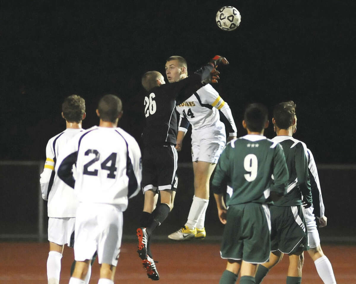 Hour photo/John Nash As players from both Simsbury, left, and Norwalk, right look on, Bears goalkeeper Tyler Dalton (26) wins this air ball battle with Trojans Connor Roche.