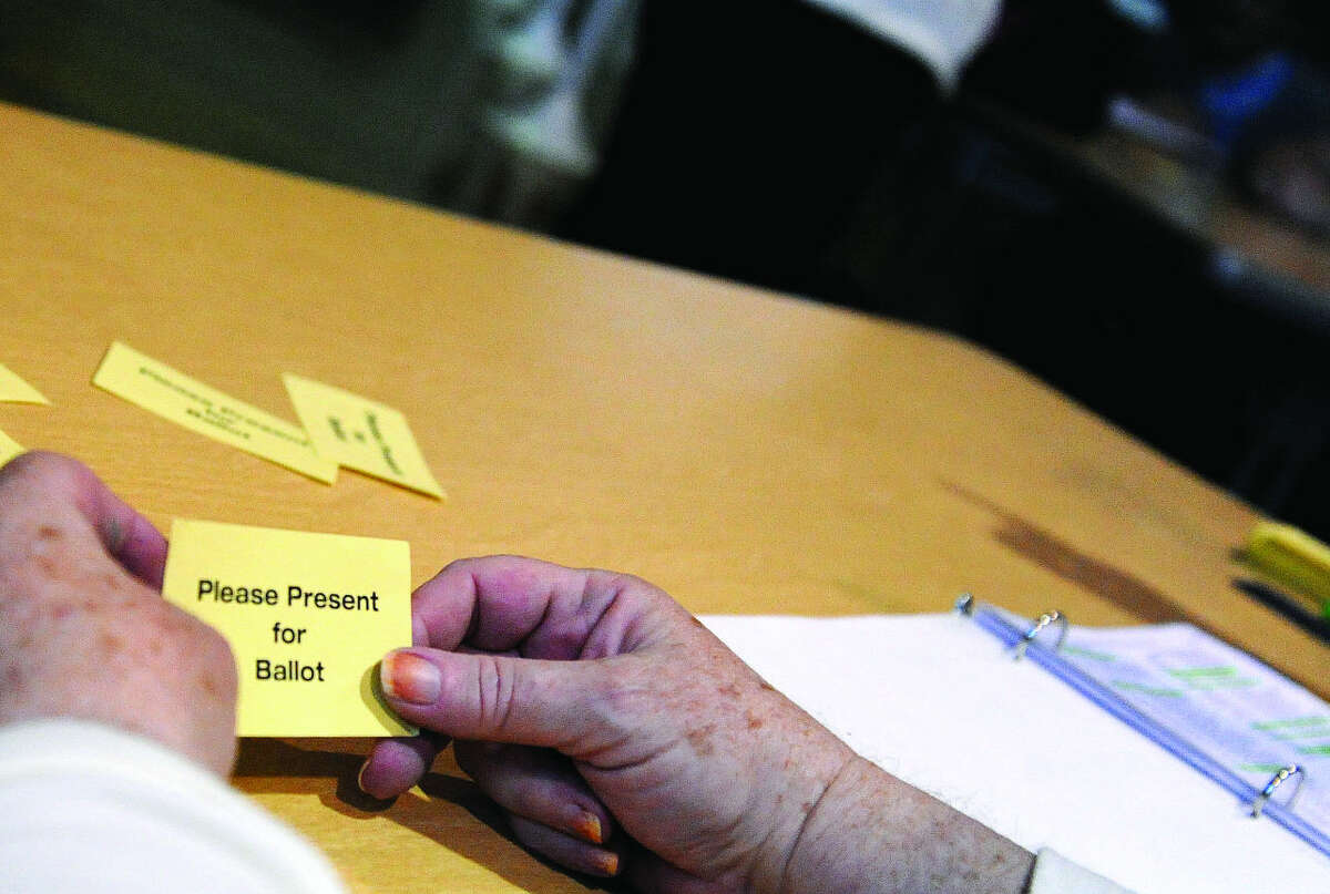 Moderators hand out stubs for voters Tuesday at Nathan Hale School on Tuesday. Hour photo/Matthew Vinci