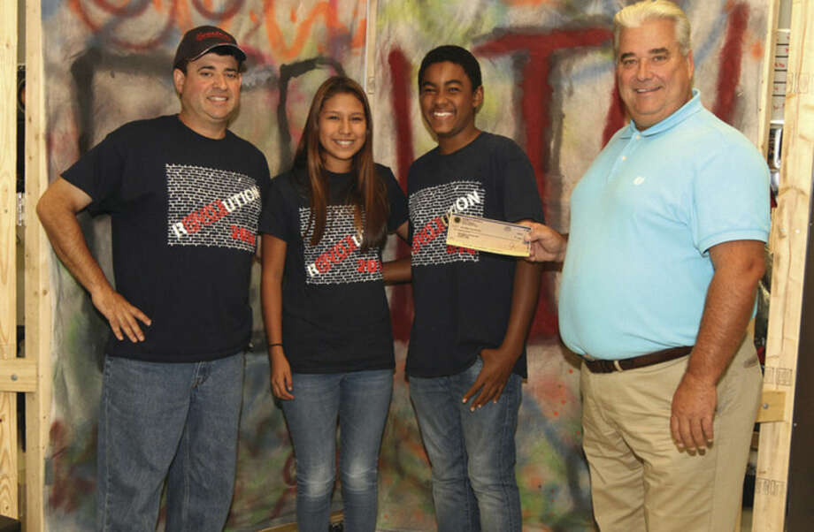 Contributed photoTim Oman (right), president of the Norwalk Exchange Club, presents a check for $1,000 to the Brien McMahon Senators Marching Band in support of the high school's program. The Exchange Club raises money from various events and donates the funds back to local community organizations. From left are Senators band director Ron Secchi, Danielle Torres, Jonathan Jadotte, and Tim Oman.
