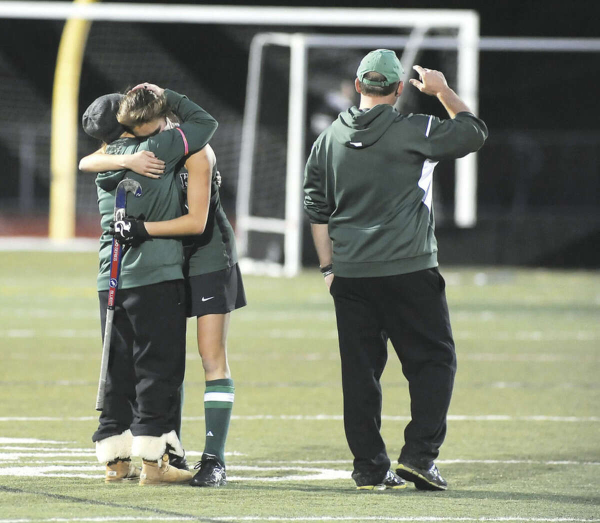 Hour photo/John Nash Norwalk senior captain Sam Bardos, second from left, embraces her assistant coach as head coach Kyle Seaburg looks off into the distance after their team's 2-1 overtime loss to Simsbury.