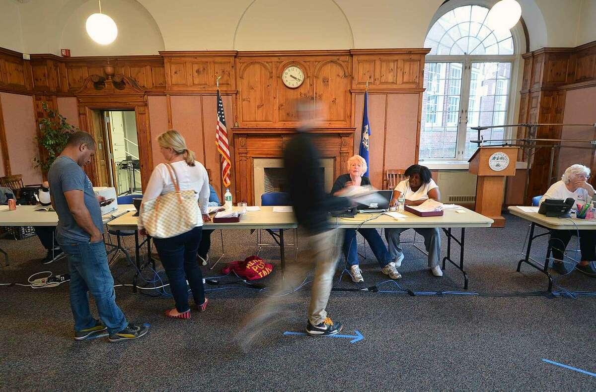 Hour Photo/Alex von Kleydorff Election Day voter registration and voting was brisk in the community room at City Hall