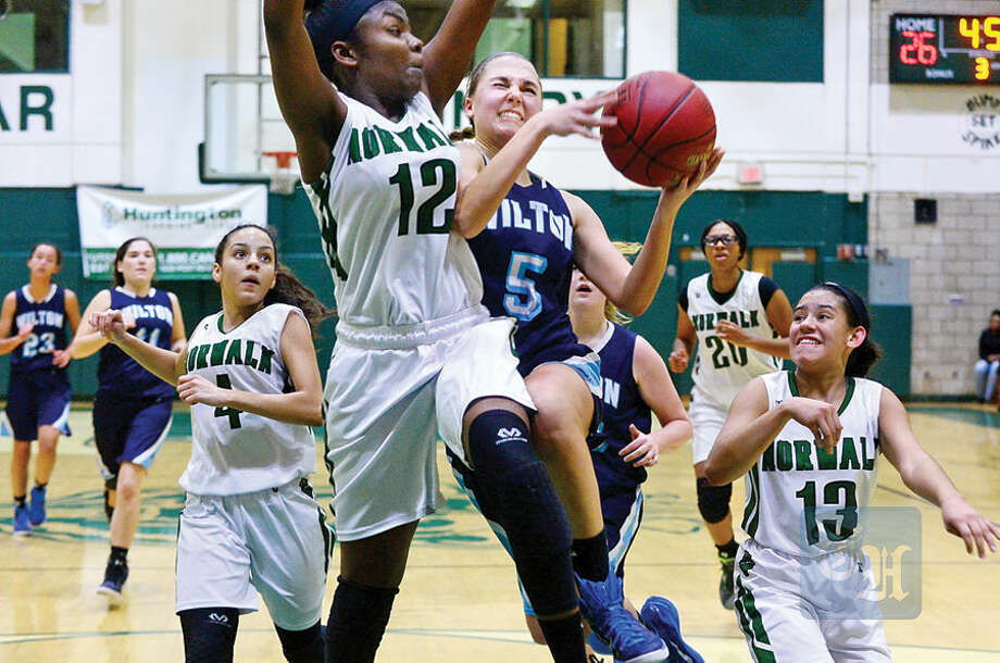 Hour photo / Erik Trautmann Wilton High School's #5 Karen Brosko tries to get as shot past Norwalk''s #12 Asiah Knight during their match up Wednesday.