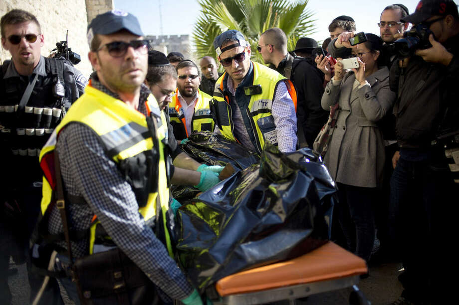 Israeli police officers evacuate the body of a Palestinian assailant form the site outside Jerusalem's Old City, Wednesday, Dec. 23, 2015. Israeli police say one Palestinian assailant was killed and a second was badly wounded after a stabbing attack on Israelis outside Jerusalem's Old City. Police spokeswoman Luba Samri says the two Palestinians attacked Jewish pedestrians outside the city's Jaffa Gate. Samri says police shot both assailants. (AP Photo/Ariel Schalit)