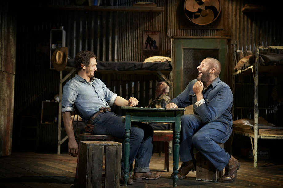 "This image released by Polk & Co. shows James Franco, left, and Chris O'Dowd in a scene from ""Of Mice and Men,"" in New York. A high-definition broadcast of Franco starring on Broadway this summer in John Steinbeck's ""Of Mice and Men"" will compete with the movies ""Nightcrawler"" and ""Gone Girl"" at the box office, and it marks an important milestone. While a few Broadway shows have been broadcast, this is the first time the National Theatre Live series, the gold standard, has chosen a Broadway show to beam into over 900 venues across the U.S. and Canada.(AP Photo/Polk & Co., Richard Phibbs)"