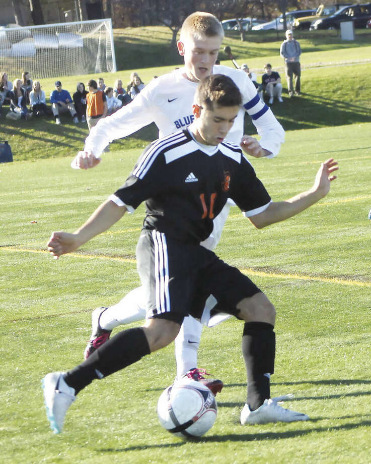 Photo by Joe RyanLuis Maradiaga of Stamford, front, controls the ball in front of a Darien defender during last week's CIAC Class LL state touranament game.