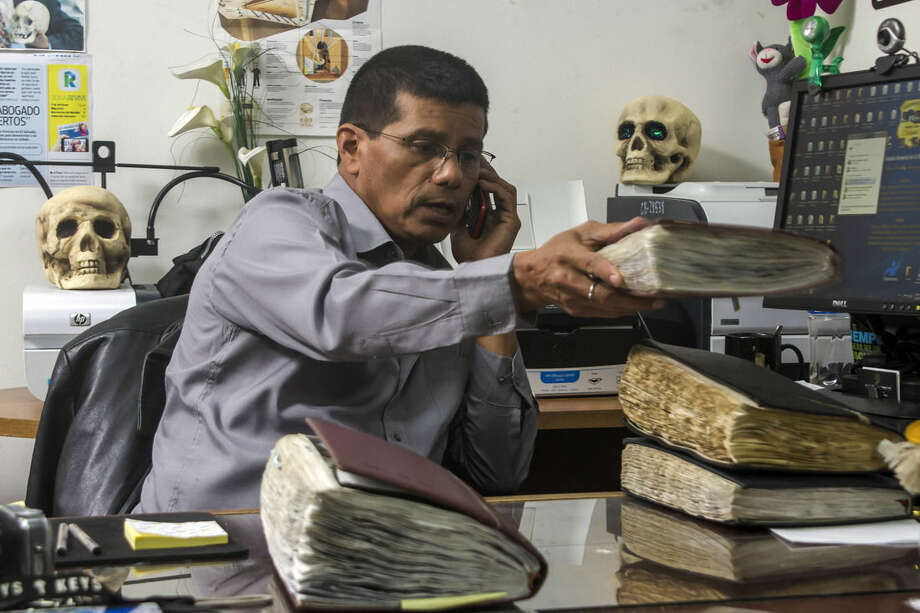 "FILE - In this Oct. 6, 2014, file photo, criminologist Israel Ticas talks on the phone as he stacks his field notebooks, at his office in San Salvador, El Salvador. Ticas, who digs up clandestine graves for the Attorney General's office, says that more than half of the 90 sites he has excavated in the last 12 years have contained the remains of murdered women and girls. ""For sure there are hundreds of these cases and maybe thousands out there,"" Ticas said. (AP Photo/Salvador Melendez, File)"