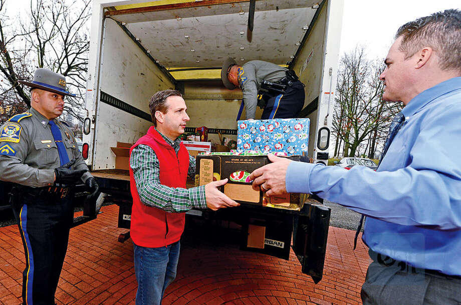 Hour photo / Erik Trautmann Connecticut State Police troppers, Johnny Barone and Dave Misenti, assist State Senate Majority Leader Bob Duff in delivering toys and food to local charities including Anthony DiLauro and The Human Services Council Wednesday.