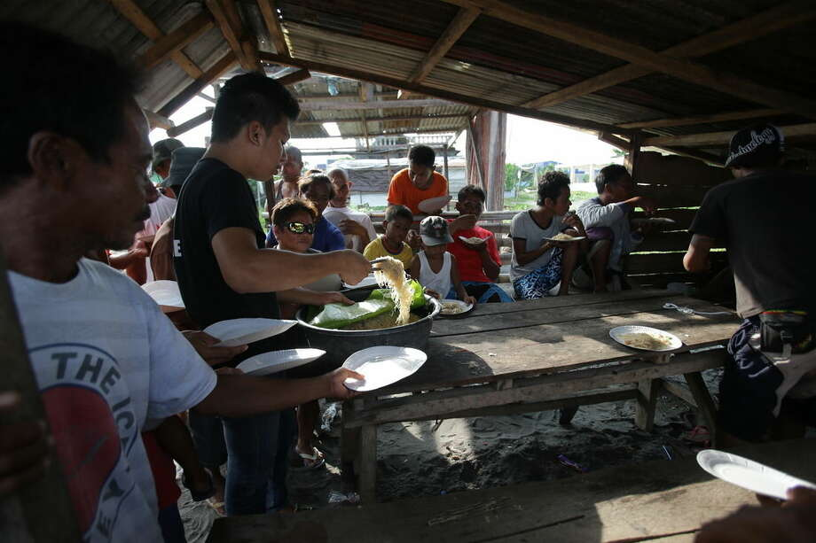 In this Oct. 11, 2014 photo, typhoon survivors eat fried noodles after blessing rites of new boats in Tanauan, Leyte province, central Philippines. Sarah Songalia, sister of David Saavedra has set up a nonprofit group called, Burublig Para Ha Tanauan, and has started projects to help villagers recover from damages during Typhoon Haiyan. The projects include distributing boats to fishermen who lost their vessels and training women to sew hospital scrubs and school uniforms. (AP Photo/Aaron Favila)