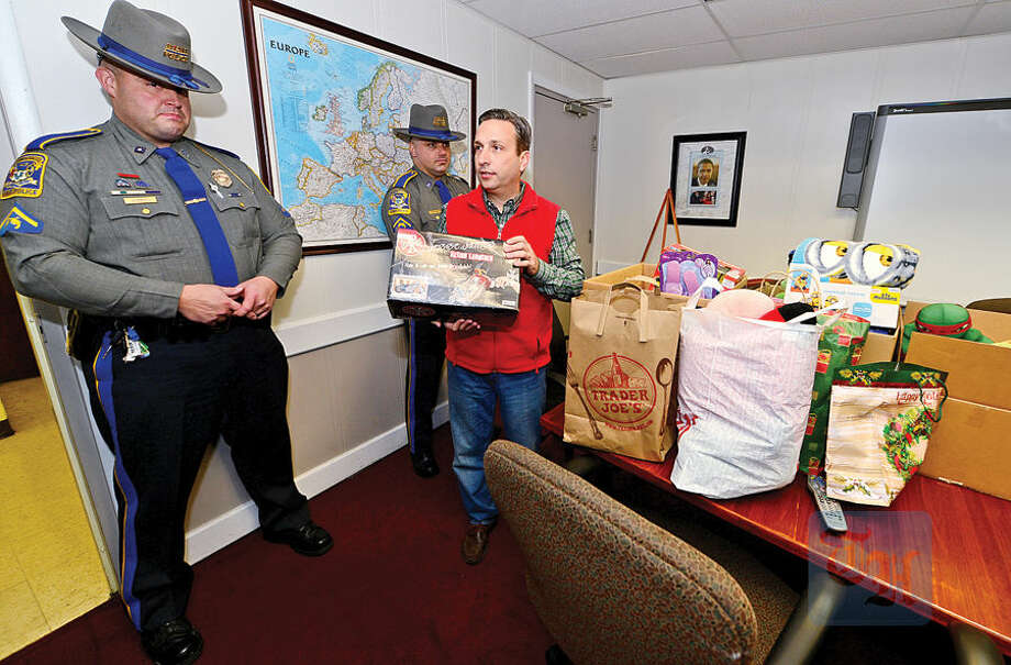 Hour photo / Erik Trautmann Connecticut State Police troopers, Johnny Barone and Dave Misenti, assist State Senate Majority Leader Bob Duff in delivering toys and food to local charities including The Carver Center Wednesday.