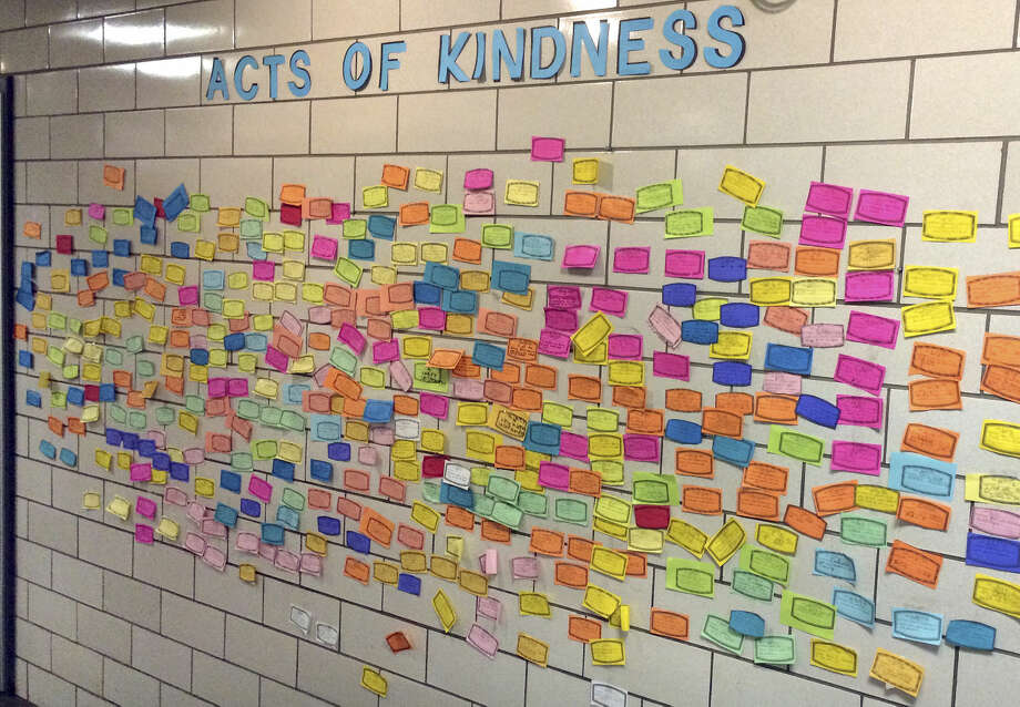 In this Dec. 1, 2015 photo, slips of paper listing acts of kindness adorn the wall of the Pleasant Valley Elementary School in South Windsor, Conn. The school is one of many across the country asking children to perform 26 acts of kindness on the third anniversary of the shooting at the Sandy Hook Elementary school that took 26 lives. The children at Pleasant Valley, many of whom are too young to remember the shooting, are not being told about the origin of the program. (AP Photo/Michael Melia)