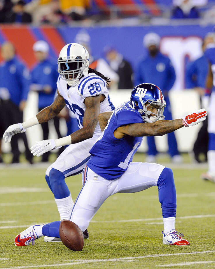 New York Giants' Odell Beckham, right, signals a first down after making a catch in front of Indianapolis Colts' Greg Toler (28) during the first half of an NFL football game Monday, Nov. 3, 2014, in East Rutherford, N.J. (AP Photo/Bill Kostroun)