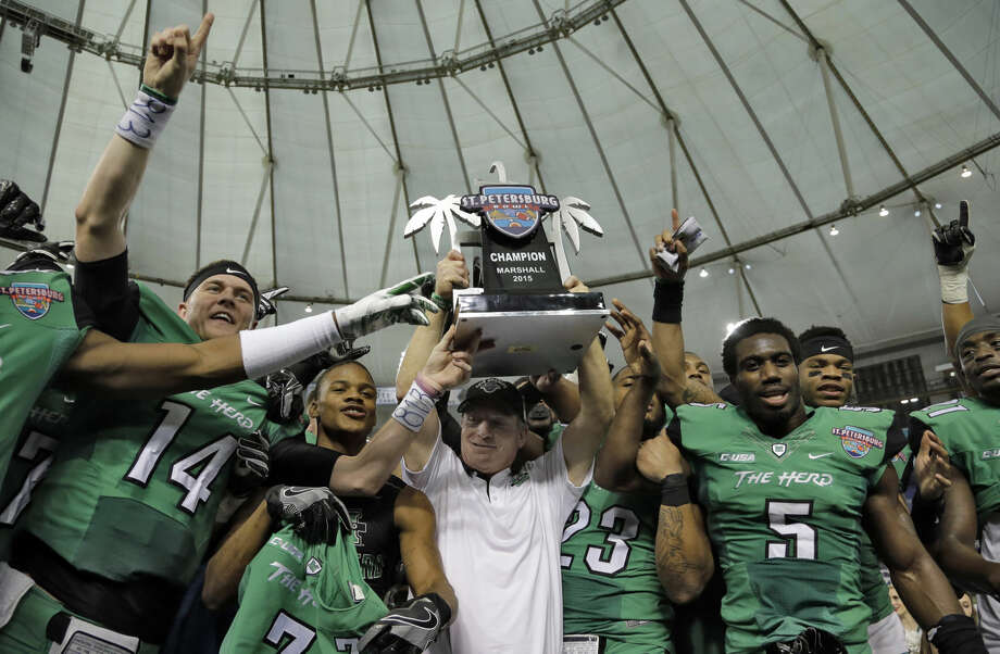 Marshall head coach Doc Holliday holds up the trophy with members of the team after defeating Connecticut 16-10 during the St. Petersburg Bowl NCAA college football game Saturday, Dec. 26, 2015, in St. Petersburg, Fla. (AP Photo/Chris O'Meara)