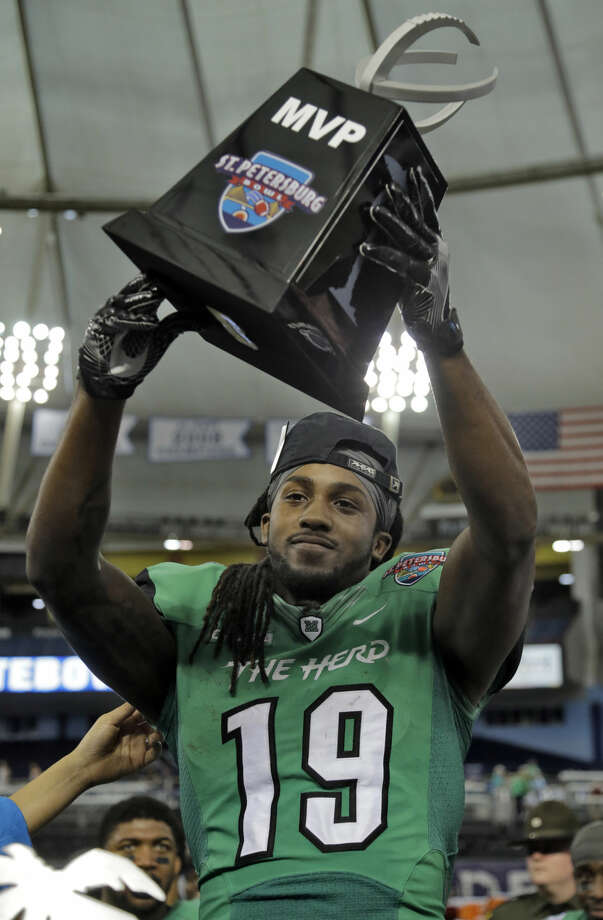 Marshall wide receiver Deandre Reaves holds up the Most Valuable Player trophy after the team defeated Connecticut 16-10 during the St. Petersburg Bowl NCAA college football game Saturday, Dec. 26, 2015, in St. Petersburg, Fla. (AP Photo/Chris O'Meara)