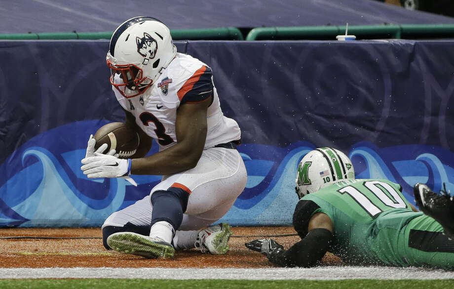Connecticut running back Ron Johnson (3) runs into the end zone after getting past Marshall defensive back Corey Tindal (10) to score during the first quarter of the St. Petersburg Bowl NCAA college football game Saturday, Dec. 26, 2015, in St. Petersburg, Fla. (AP Photo/Chris O'Meara)