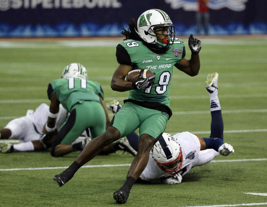 Marshall wide receiver Deandre Reaves (19) eludes a tackle by Connecticut linebacker Vontae Diggs during the first quarter of the St. Petersburg Bowl NCAA college football game, Saturday, Dec. 26, 2015, in St. Petersburg, Fla. (AP Photo/Chris O'Meara)