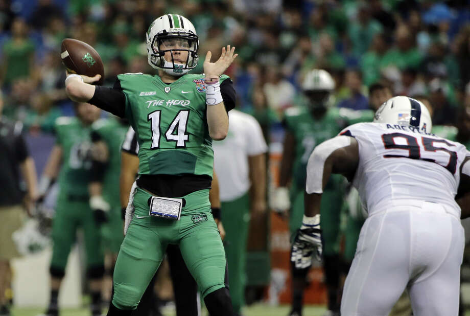 Marshall quarterback Chase Litton (14) is pressured by Connecticut defensive lineman Kenton Adeyemi (95) as he throws a touchdown pass to tight end Ryan Yurachek during the first quarter of the St. Petersburg Bowl NCAA college football game, Saturday, Dec. 26, 2015, in St. Petersburg, Fla. (AP Photo/Chris O'Meara)