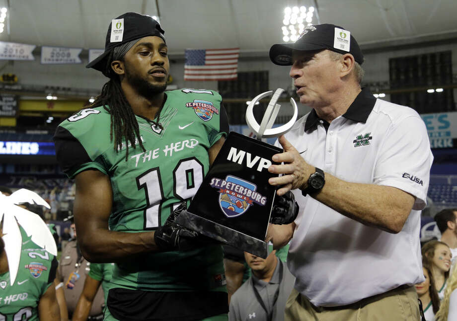 Marshall head coach Doc Holliday, right, hands wide receiver Deandre Reaves (19) the trophy for being the Most Valuable Player during the St. Petersburg Bowl NCAA college football game against Connecticut Saturday, Dec. 26, 2015, in St. Petersburg, Fla. Marshall won the game 16-10. (AP Photo/Chris O'Meara)