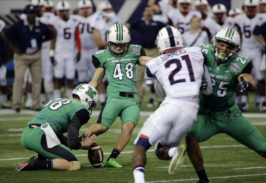 Marshall place kicker Nick Smith (48) kicks a field goal against Connecticut during the fourth quarter of the St. Petersburg Bowl NCAA college football game Saturday, Dec. 26, 2015, in St. Petersburg, Fla. Marshall won the game 16-10. Holding for Smith is Tyler Williams (38). (AP Photo/Chris O'Meara)