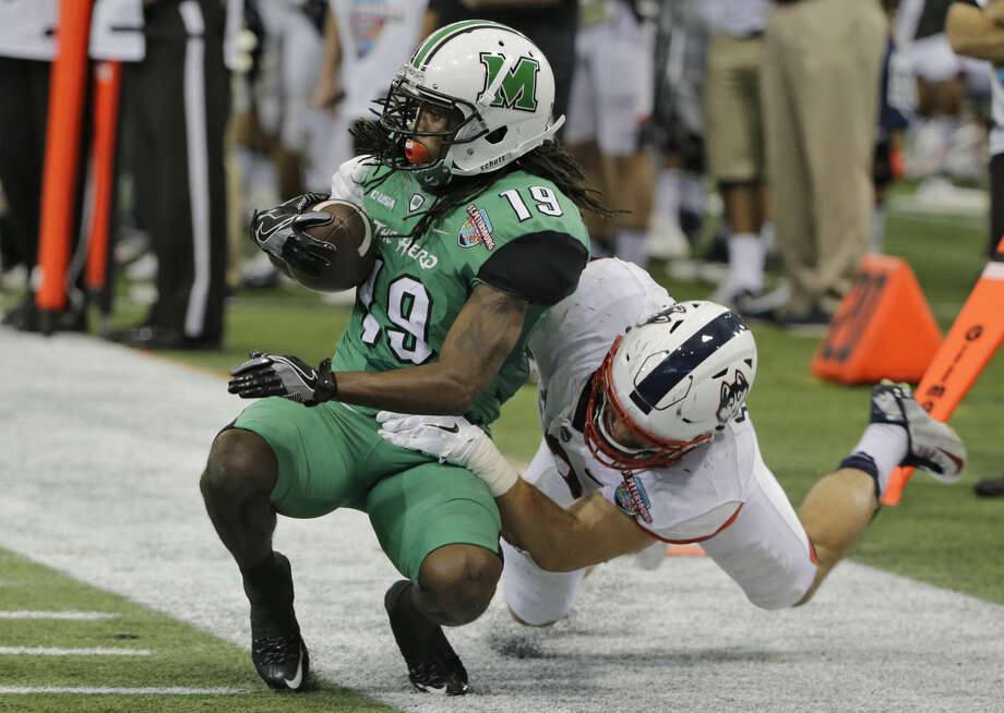 Marshall wide receiver Deandre Reaves (19) gets pulled down by Connecticut linebacker Graham Stewart (2) during the first half of the St. Petersburg Bowl NCAA college football game Saturday, Dec. 26, 2015, in St. Petersburg, Fla. Reaves was named the games Most Valuable Player. (AP Photo/Chris O'Meara)