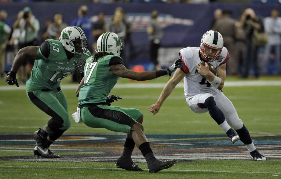 Connecticut quarterback Bryant Shirreffs (4) cuts back in front of Marshall defensive lineman Armonze Daniel (13) and safety Taj Letman (17) during the St. Petersburg Bowl NCAA college football game Saturday, Dec. 26, 2015, in St. Petersburg, Fla. (AP Photo/Chris O'Meara)