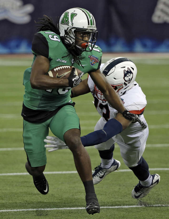 Marshall wide receiver Deandre Reaves (19) slips a tackle by Connecticut linebacker Vontae Diggs (13) during the St. Petersburg Bowl NCAA college football game Saturday, Dec. 26, 2015, in St. Petersburg, Fla. (AP Photo/Chris O'Meara)